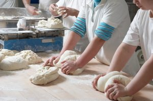 Women bakery team at work weigh and mixing dough